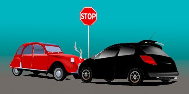 Dos coches chocando junto a señal de Stop