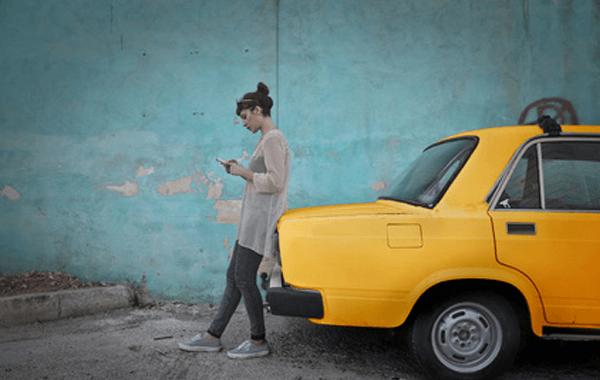 mujer con su móvil asegurando su coche amarillo