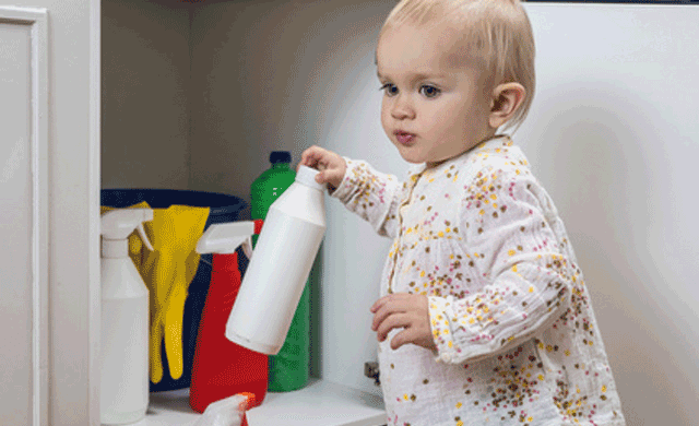 bebe cogiendo productos de limpieza en casa