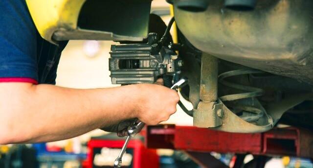 mecánico trabajando en coche dentro del taller