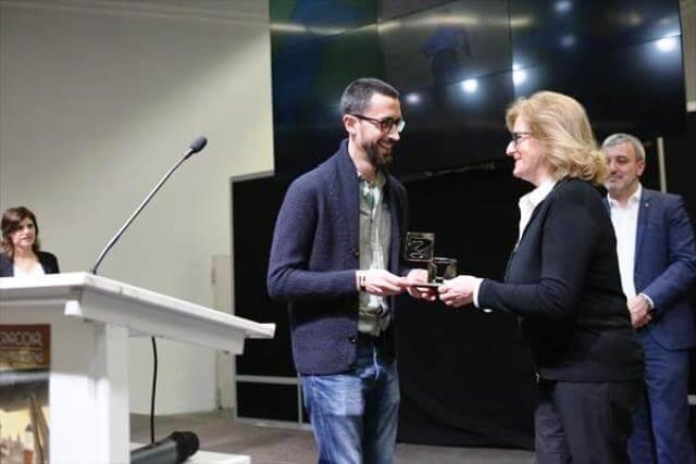 Javi Rey recogiendo el premio a mejor autor revelación de manos de Rosa Laparra (Fundación Divina Pastora)