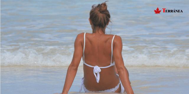 mujer tomando el sol en la playa para ponerse moreno