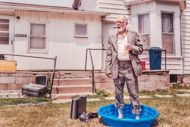 Hombre mayor fumando puro y tomando un whisky mientras se relaja al sol veraniego en su mini piscina