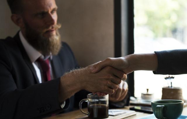 Apretón de manos entre asegurador y tomador al contratar su póliza de seguro