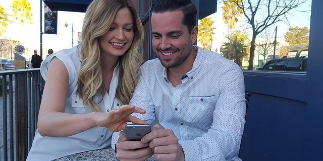 Dos amigos haciendo una consulta en el móvil.