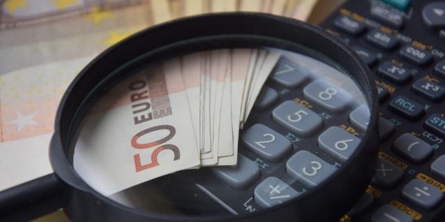 Billetes, calculadora y lupa colocados en una mesa para ser fotografiados. Representan la fiabilidad y precisión del sector asegurador