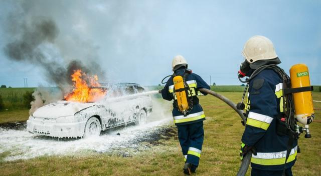 Coche incendiándose mientras los bomberos lo intentan apagr
