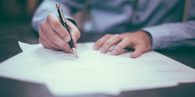 Hombre firmando un contrato con una aseguradora