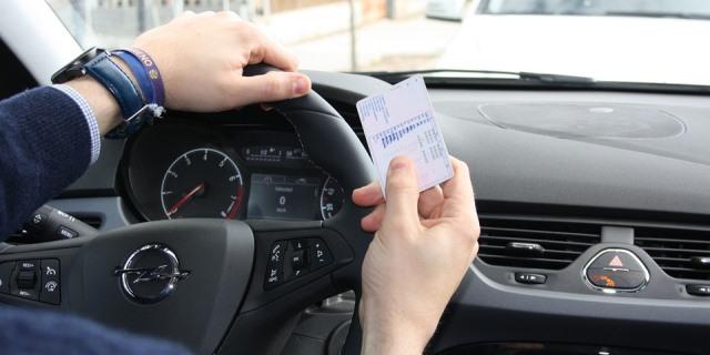 Hombre que sujeta su carné de conducir mientras circula