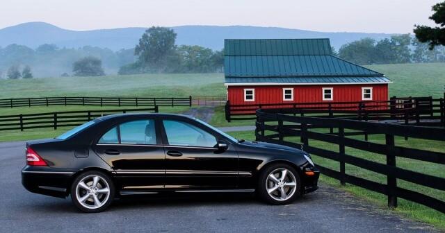 Mercedes negro aparcado al lado de una granja