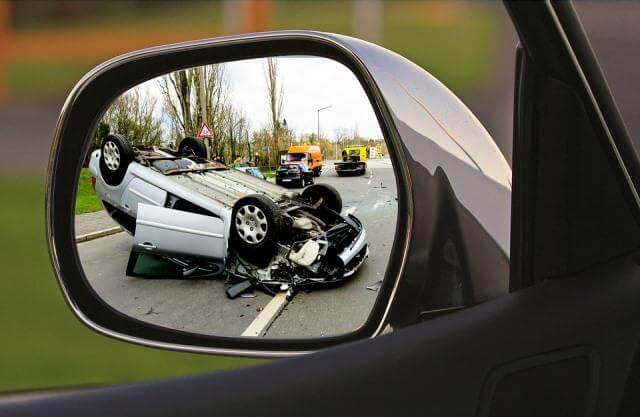 Retrovisor reflejando un coche volcado en un accidente
