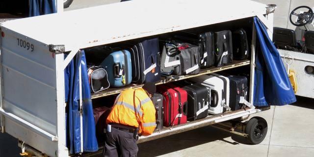 Hombre cargando las maletas facturadas en un avión. La pérdida de las mismas es una de las coberturas que te proporciona el seguro de viaje.