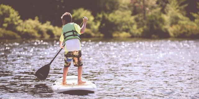 Niño realizando paddle surf en un pantano.