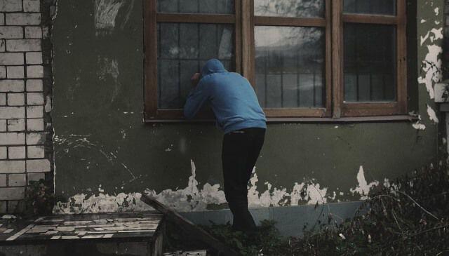 Ladrón mirando por la ventana de una casa deshabitada por vacaciones.