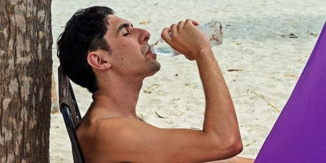 Hombre sentado mientras bebe agua.