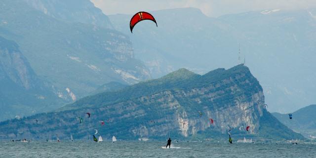 Varias personas practicando kitesurf con un un peñón de fondo