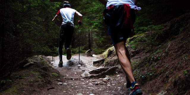 Dos hombres corriendo en un sendero un día de verano.