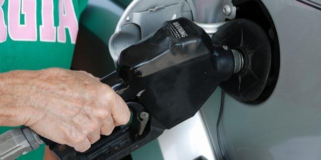 Hombre echando gasolina a su vehículo.