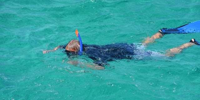 Niño haciendo esnórquel en una playa con aguas transparentes.