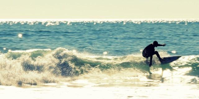 Hombre haciendo surf en una bonita playa con un oleaje moderado.