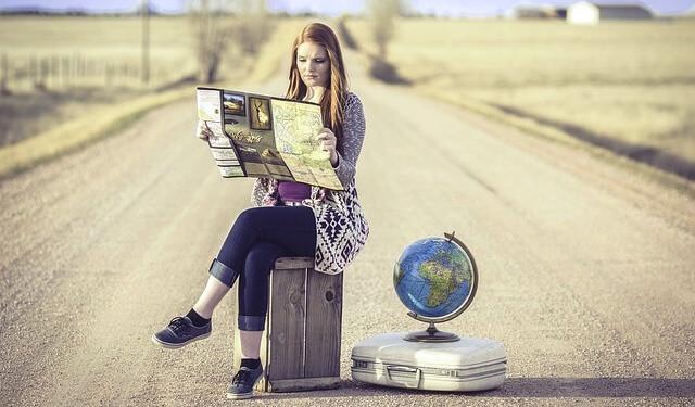 Pelirroja preparando su viaje internacional por carretera con un mapa del mundo