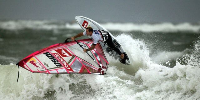 Profesional del windsurf realizando una bonita maniobra sobre una ola.