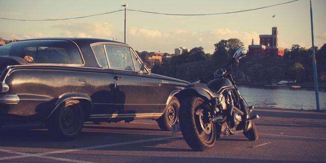 Moto y coche clásicos aparcados en paralelo.
