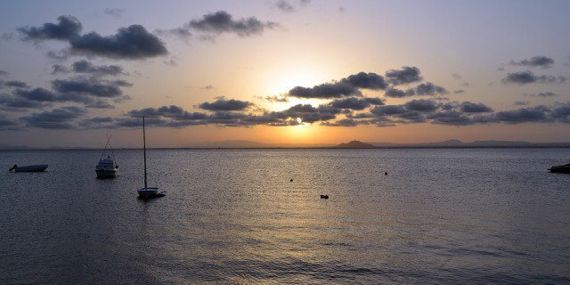 Atardecer en mar Menor con varios barcos e islas de fondo.