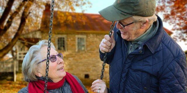 Una pareja de ancianos mirándose mientras se encuentran en un columpio.