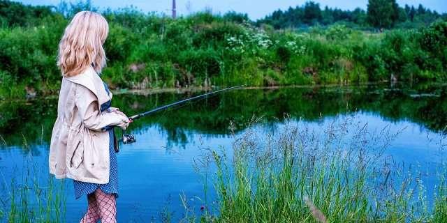 Mujer pescando en la orilla de un estanque.