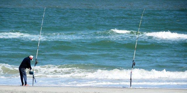 Hombre practicando surfcasting en la orilla de una playa.