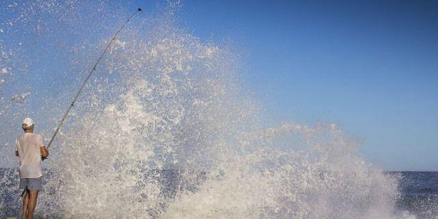 Hombre pescando mientras una ola rompe en la costa donde se encuentra.