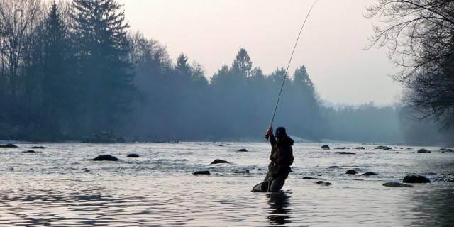 Pescador tirando la caña en un río.