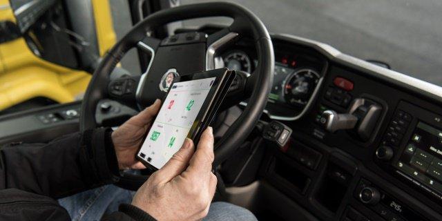 Uno de los transportistas sujetando una tablet dentro de su camión.