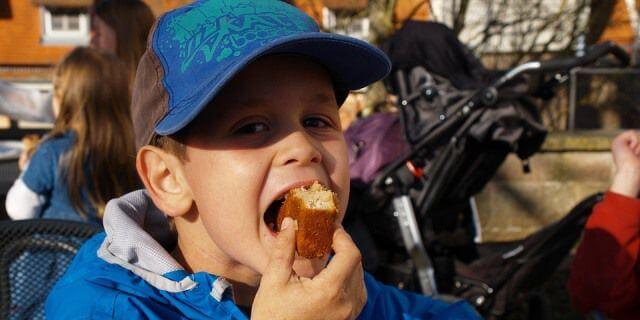Niño comiendo bollería industrial. La bollería industrial no debe formar la alimentación de los niños.