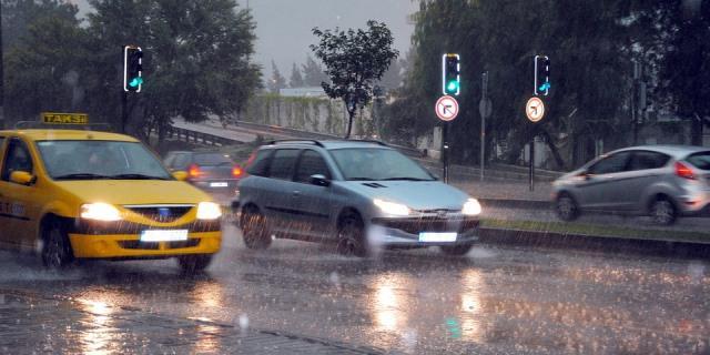 Coches atravesando un charco creado por la fuerte lluvia en una ciudad.