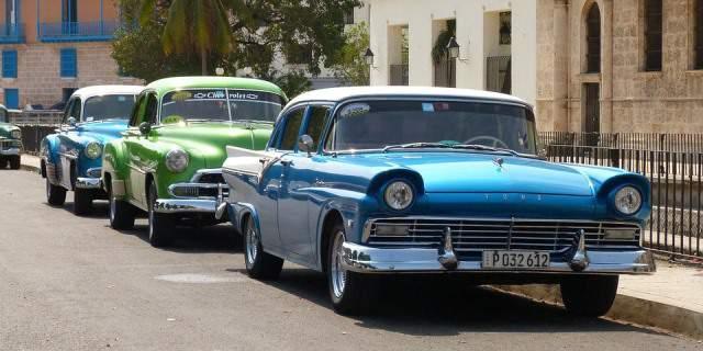 Tres coches clásicos aparcados en una calle en fila.
