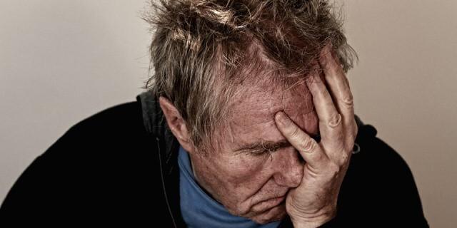 Hombre que tiene depresión se lleva la mano a la cara.
