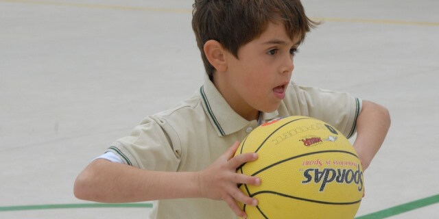 Niño jugando al baloncesto.