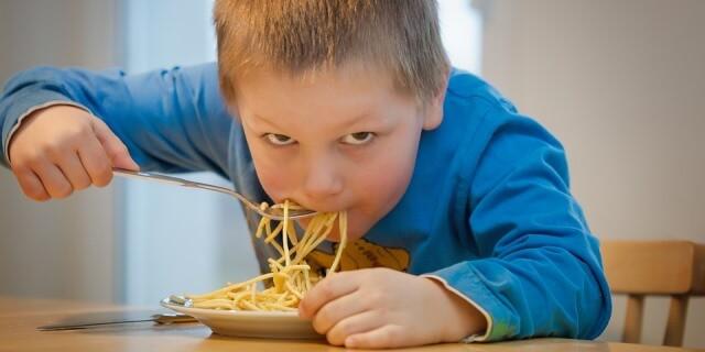 Niño comiendo espaguetis.