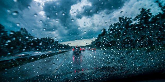 Parabrisas mojado mientras el coche circula por una carretera secundaria.