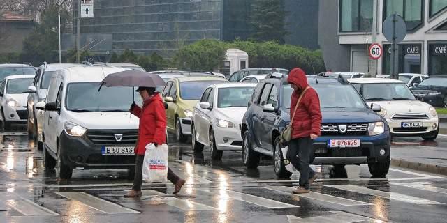 Peatones cruzando un paso de cebra mientras llueve.