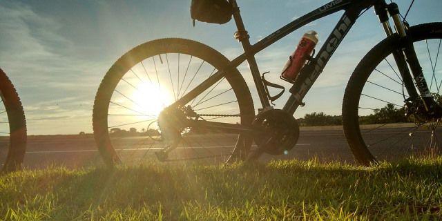 Bicicleta en un parque con el sol de fondo.