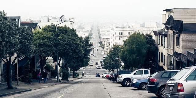 Calle en rampa con coches aparcados a un lado.