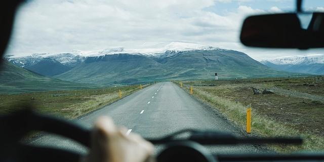 Persona conduciendo que contempla un sistema montañoso en el fondo do la carretera.