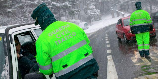 Dos agentes de la Guardia Civil parando el tráfico mientras nieva.
