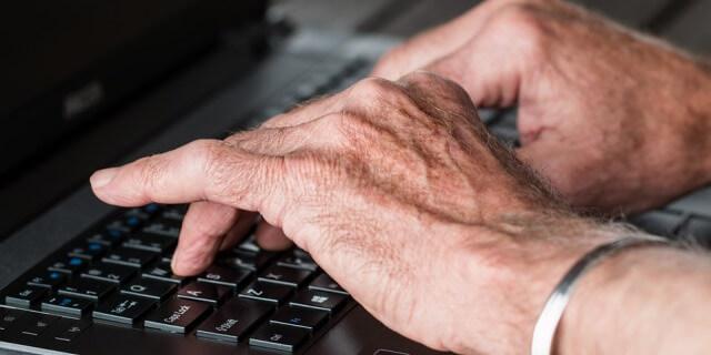 Hombre tecleando un ordenador portátil.