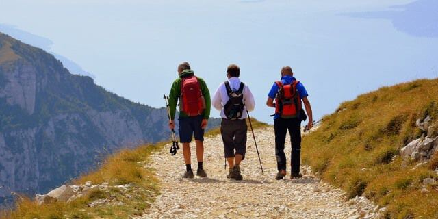 Tres hombres de espaldas practicando senderismo.