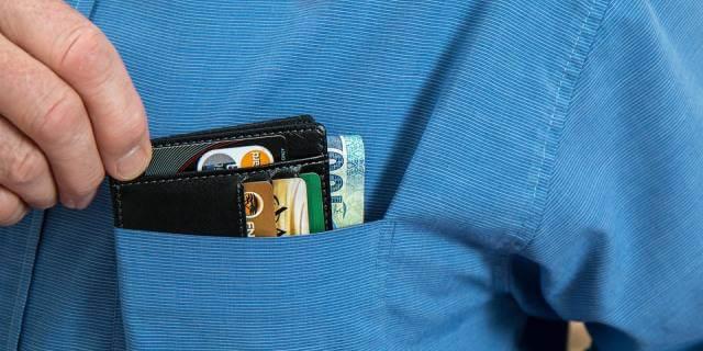 Hombre sacándose la cartera del bolsillo de su camisa.