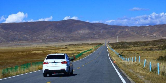 Monovolumen blanco circulando en una carretera secundaria de China.